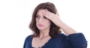 Mulher com dor de cabeça, um dos sintomas da menopausa