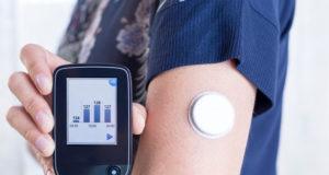 mulher fazendo exames de rotina no braço com aparelho digital