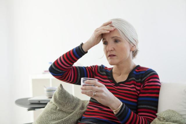 mulher com a mãe na cabeça sentindo os sintomas do climatério