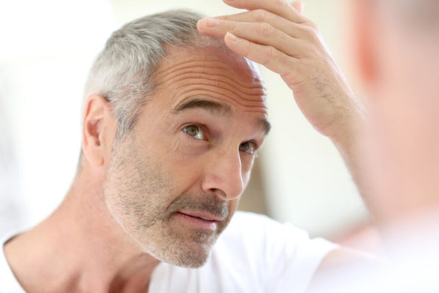 Homem procurando remédios para a queda de cabelo