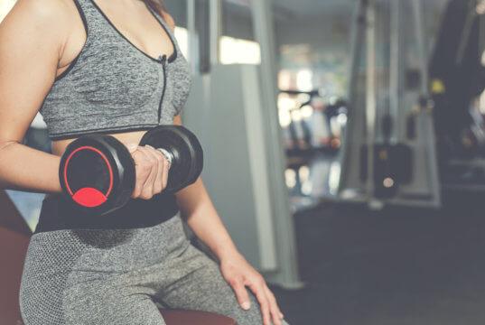 Mulher praticando musculação para auxiliar o metabolismo