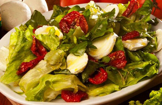 Salada verde com muçarela de búfala e tomates secos.